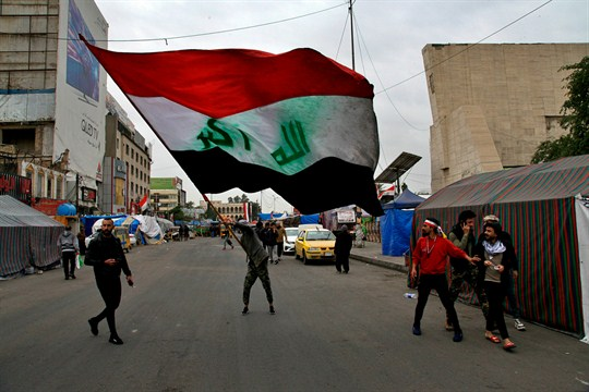A man waves an Iraqi flag during anti-government demonstrations in Tahrir Square, Baghdad.