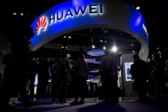 Visitors look at a display from Chinese technology firm Huawei at the PT Expo in Beijing