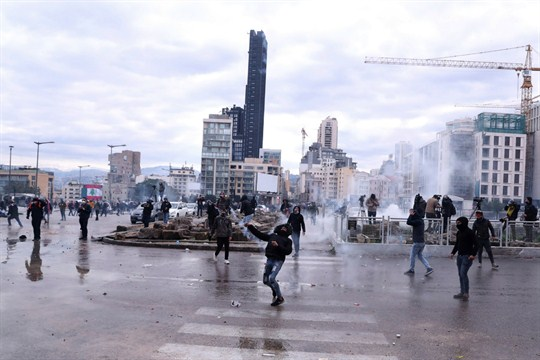 Anti-government demonstrators throw tear gas canisters back at riot police during a protest in downtown Beirut.