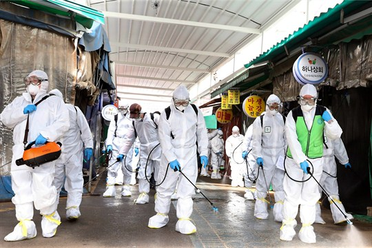 Workers wearing protective suits spray disinfectant at a market in Bupyeong, South Korea.