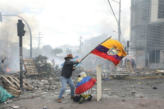 An anti-government demonstrator waves an Ecuadorian national flag during clashes with police in Quito, Ecuador.