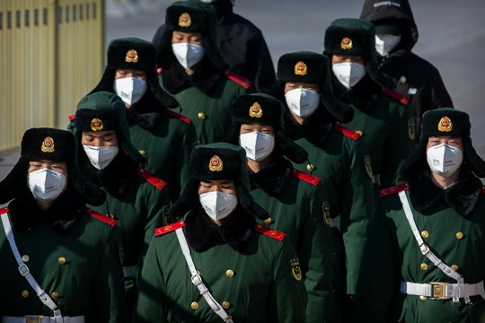 Paramilitary policemen wear face masks as they march in formation near Tiananmen Square in Beijing.