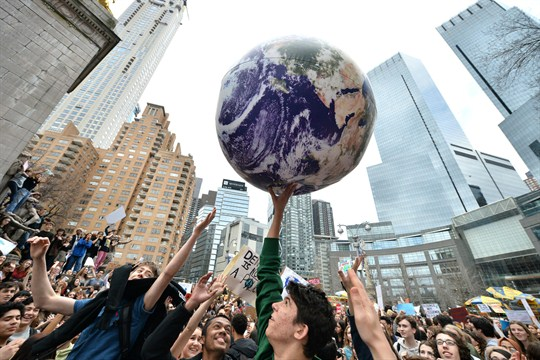 A student protester holds up a foam replica of the earth during the Youth Climate Strike