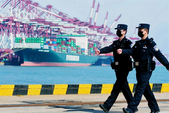 Police officers wearing face masks patrol at a container port in Qingdao, China.