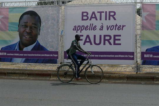 A man rides a bicycle past election posters of Togo's president, Faure Gnassingbe, in Lome, Togo.