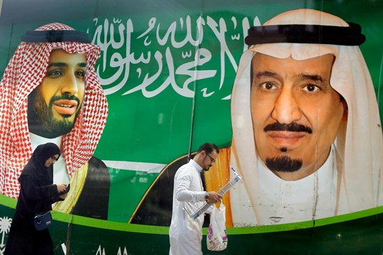 People walk past a banner showing Saudi King Salman and Crown Prince Mohammed bin Salman