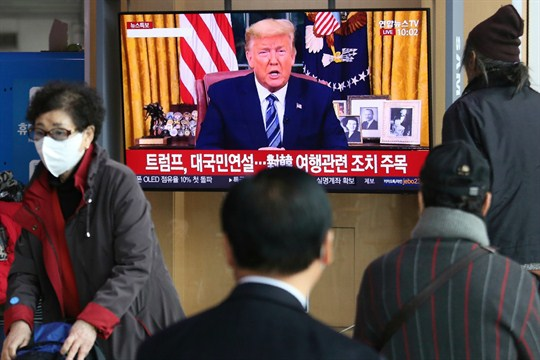 People watch a TV showing a live broadcast of President Trump's speech, in Seoul, South Korea.