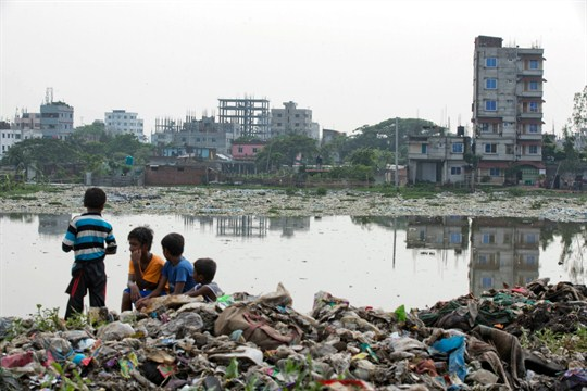 Bangladeshi children sit on garbage piled up by the Buriganga River in Dhaka, Bangladesh