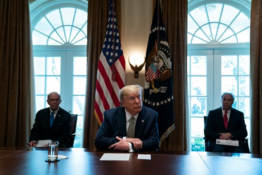 President Donald Trump listens during a meeting with tourism industry executives about the COVID-19 pandemic