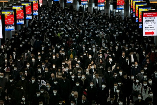 A large crowd wearing masks commutes through Shinagawa Station in Tokyo, Japan