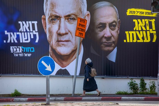 A woman walks by a campaign billboard for the opposition Blue and White party in Israel