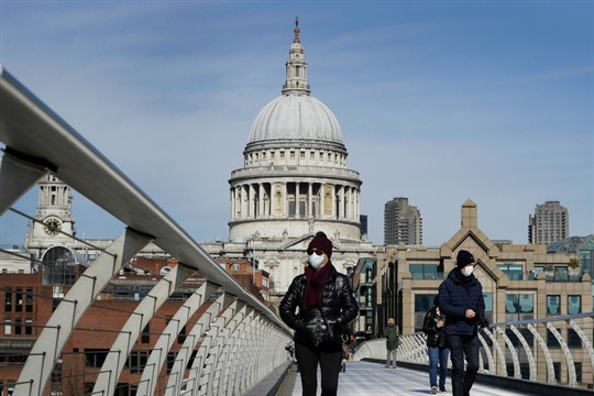People wear masks as they walk over Millennium Bridge near St Paul's Cathedral, London.