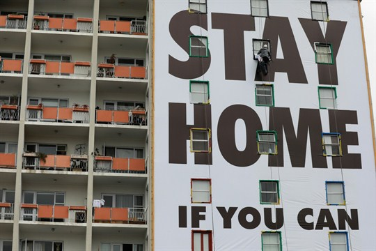 "A billboard that reads ""Stay Home if You Can"" on an apartment building in Cape Town."