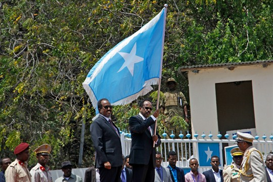 Somali President Mohamed Ahmed Mohammad holds a national flag during a handover ceremony in 2017.