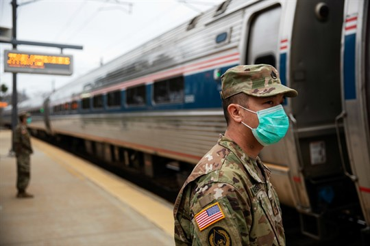 Members of the Rhode Island National Guard look for passengers getting off a train.