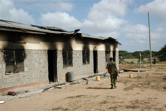 A Kenyan soldier walks past a damaged police post after an attack by al-Shabab