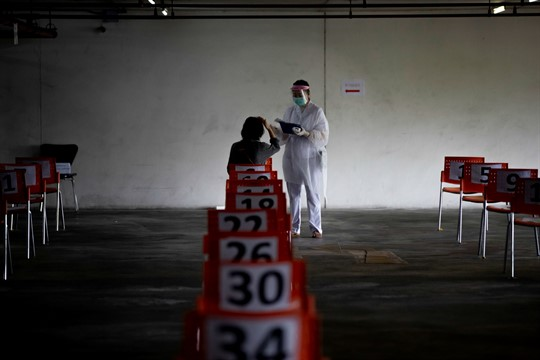 A nurse attends to a woman at a COVID-19 screening center at Chulalongkorn University in Thailand.