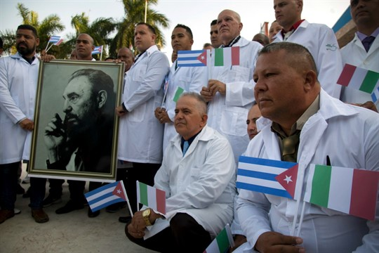 Cuban doctors and medical professionals pose with a photo of Fidel Castro before departing for Italy.