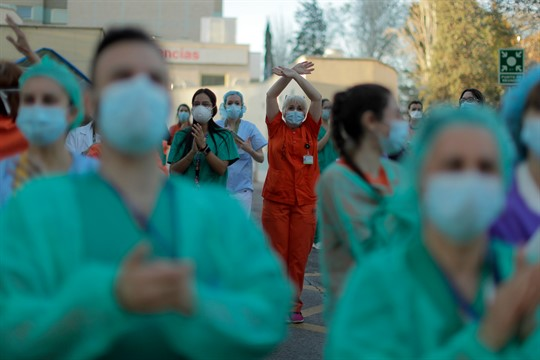 Health workers react as people applaud from their houses in Madrid