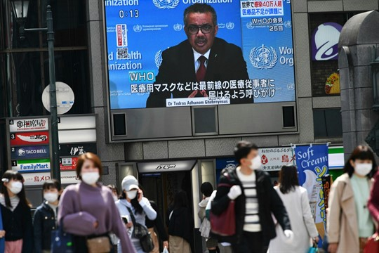 A monitor shows World Health Organization Director-General Tedros Adhanom Ghebreyesus, in Osaka, Japan.
