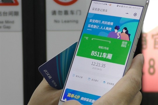 A subway passenger holds up a green code on their phone in Wuhan, China.