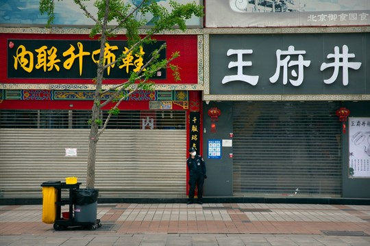 A security guard stands next to shuttered shops in Beijing, China.