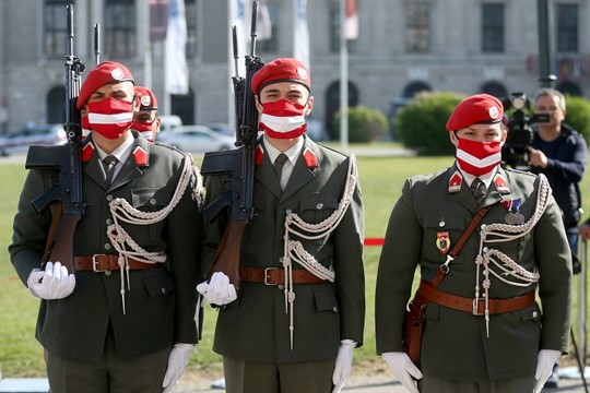 Austrian soldiers wearing protective masks at a military ceremony in Vienna.
