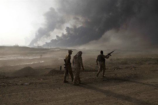 Iraqi soldiers man a checkpoint as oil wells burn on the outskirts of Qayyarah, Iraq.
