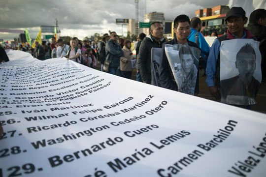 Demonstrators hold a banner with the names of murdered activists during a protest march in Colombia
