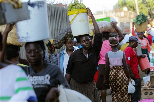 Women carry food at a local market in Harare, Zimbabwe.