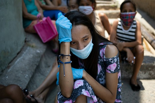 A woman wearing a mask and gloves waits outside a soup kitchen in Caracas, Venezuela