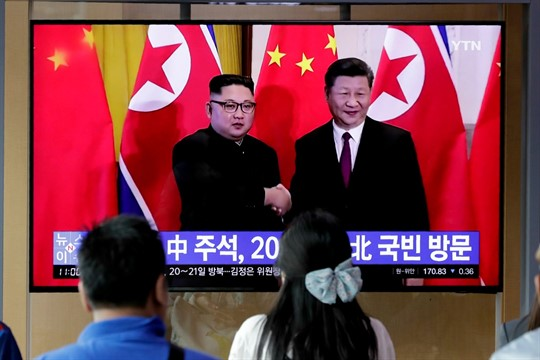 People watch a news program about Chinese President Xi Jinping's state visit to North Korea