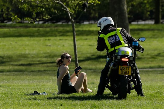 A woman is told to go home by a police officer on a motorbike in London