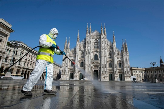 A worker sprays disinfectant to sanitize Duomo square in Milan, Italy