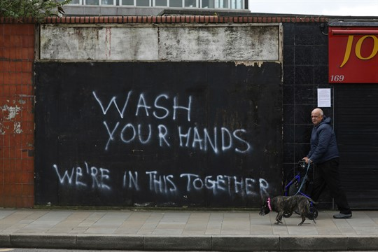 A man walks his dog past graffiti calling for people to wash their hands, in Belfast