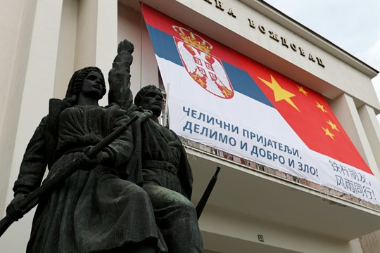 """A billboard showing Serbian and Chinese flags reading: """"Iron friends, together in good and evil!"""""""