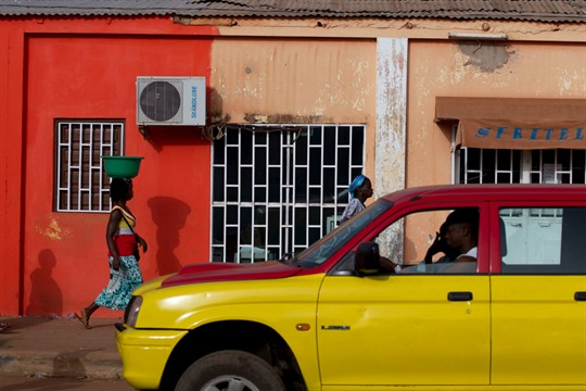 A car passes as women return from a fishing port in central Bissau, Guinea-Bissau.