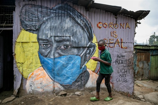 A boy wearing a mask walks past a mural warning people about the coronavirus, in Nairobi