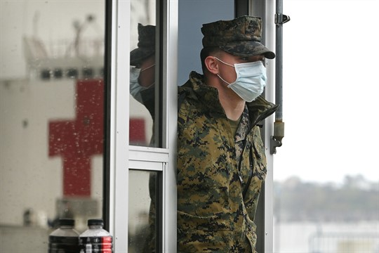 A U.S. Marine stands guard as the USNS Comfort hospital ship prepares to leave New York