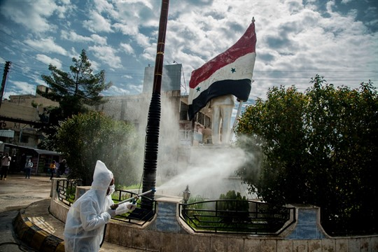 Workers disinfect the streets to prevent the spread of coronavirus in Qamishli, Syria.