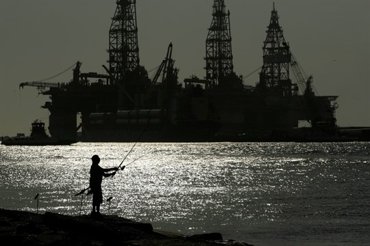 A man fishes near docked oil drilling platforms, in Port Aransas, Texas.