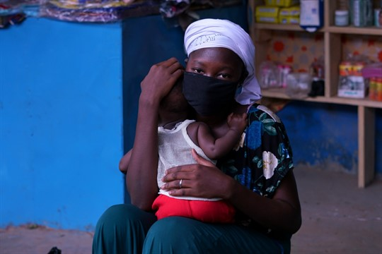 A woman wearing a face mask holds her child at a marketplace in Ouagadougou, Burkina Faso.