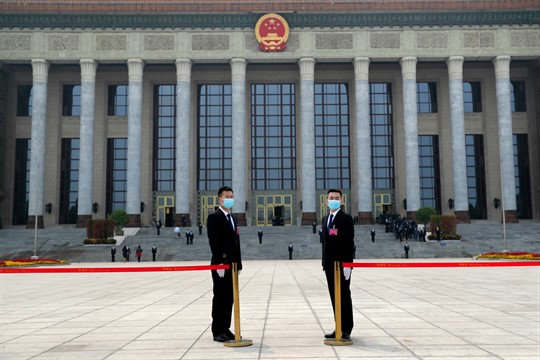Security officers wearing face masks stand guard outside before the opening session of the CPPCC