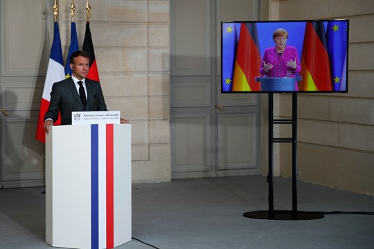 Emmanuel Macron listens to Angela Merkel during a joint video press conference at the Elysee Palace