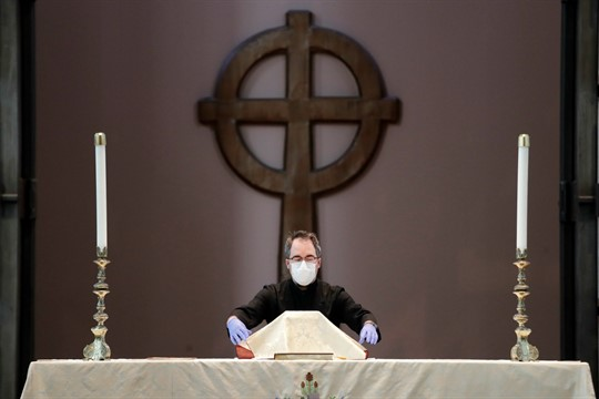 A sacristan prepares the altar for a livestream Easter service at a church in Seattle