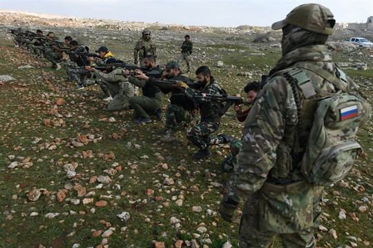 A Russian instructor trains Syrian soldiers and militia members at a training camp in Aleppo province