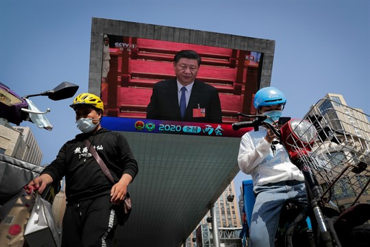 Food delivery workers near a TV screen showing Xi Jinping at the National People's Congress, Beijing