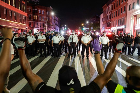Protesters take a knee in front of New York City police officers during a demonstration