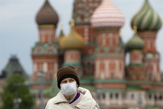 A woman walks near Red Square with St. Basil's Cathedral in the background in Moscow