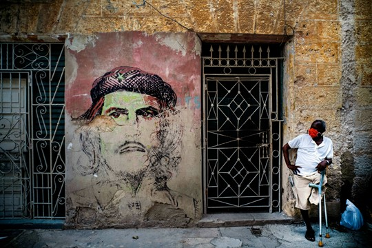 A man rests in the shade against a wall covered with a mural of Che Guevara.